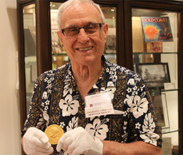 Legacy Society member Dean Wilson holding National Medal of Science at Leatherby Libraries
